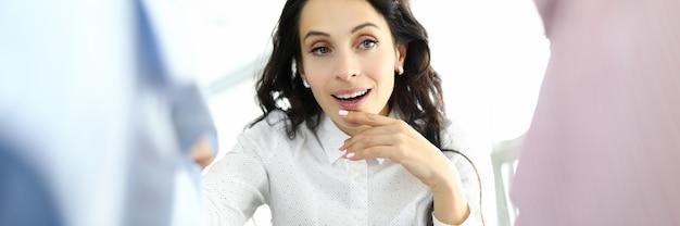 Vrouw met peinzende blik kiest kleren op hanger