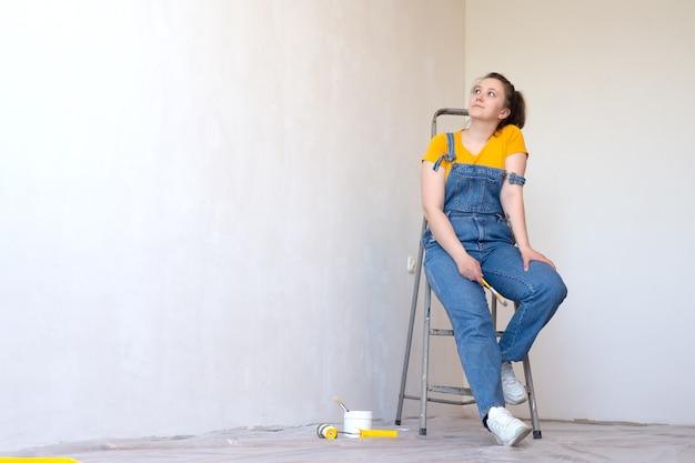 Vrouw met penseel en ladder kijkt dromerig in een kamer met een ongeverfde muur met kopieerruimte copy