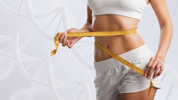 Vrouw met perfect lichaam in de buurt van dna-stengels. afslankconcept. verbetering van het metabolismeconcept.