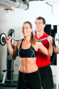 Vrouw met persoonlijke trainer in de sportschool