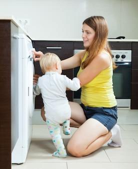 Vrouw met peuter die wasmachine met behulp van