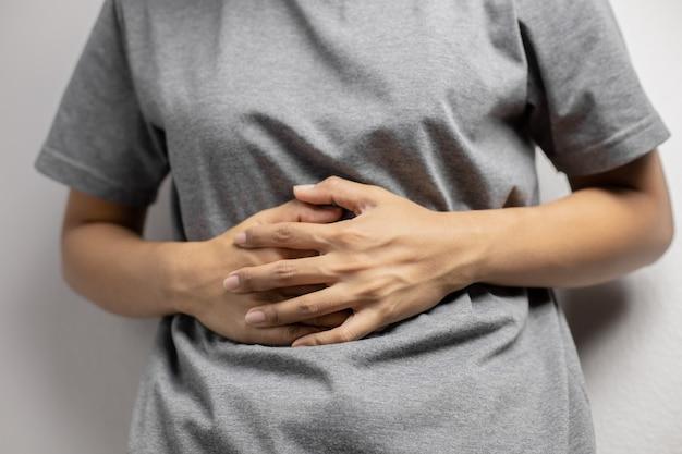 Vrouw met pijnlijke buikpijn. jonge vrouw met buikpijn als gevolg van menstruatie. buikpijn als gevolg van gastritis.