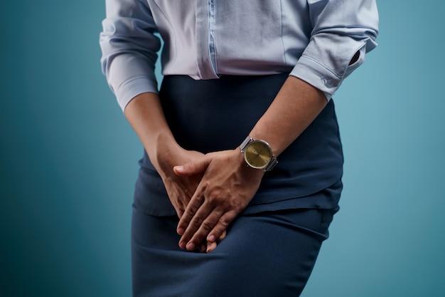 Vrouw met pijnlijke hand in hand op haar kruis onderbuik te drukken