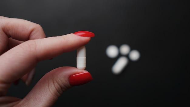 Vrouw met pil, capsule in de hand close-up van de arts. concept van medicatie, drugstesten. epidemie en virusconcept