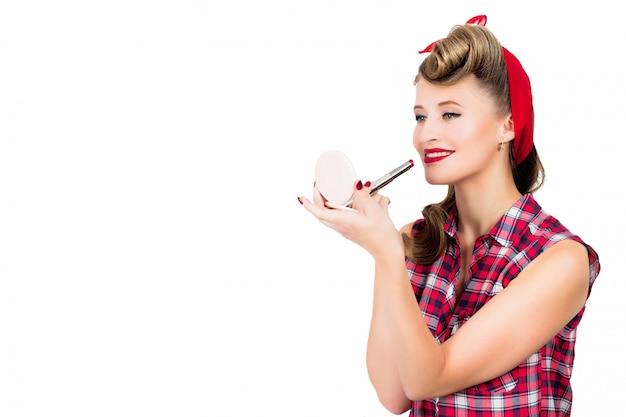 Vrouw met pin-up kapsel bedrijf spiegel