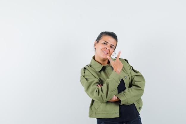 Vrouw met pistoolgebaar in jasje, t-shirt en op zoek naar vertrouwen.