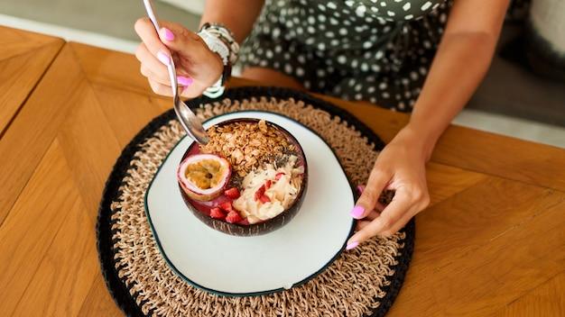 Vrouw met plaat kokosnoot plaat met smakelijke smoothie kom.