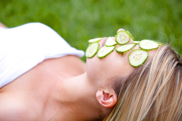 Vrouw met plakjes komkommer over haar gezicht