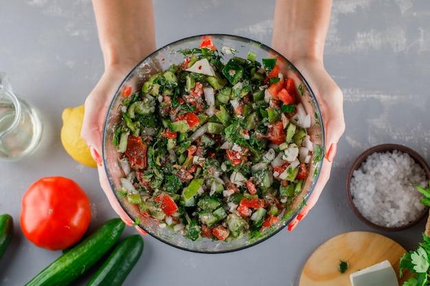 Vrouw met plantaardige salade met tomaten, kaas, komkommer, zout in een glazen kom op grijze ondergrond, bovenaanzicht