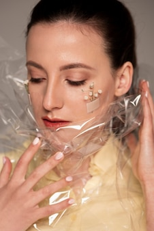 Vrouw met pleisterbloem en pplastic op gezicht