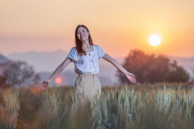Vrouw met plezier op gerst veld op zonsondergang tijd