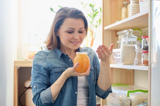 Vrouw met pot gouden biologische verse honing in de keuken