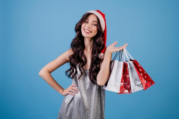 Vrouw met presenteert in boodschappentassen dragen kerstmuts