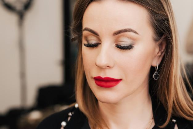 Vrouw met professionele lichte make-up met rode lippenstift in een schoonheidssalon