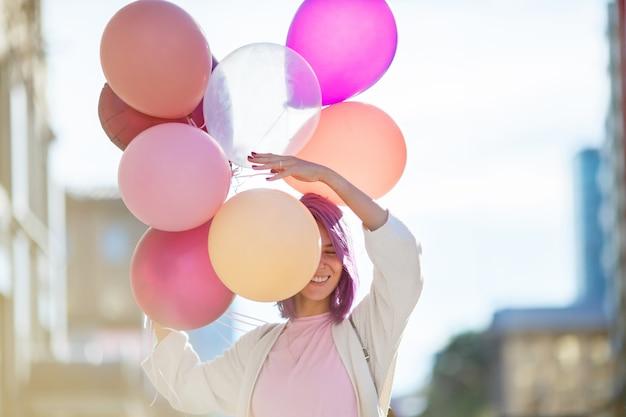 Vrouw met purper haar dat zich in de stadsstraat bevindt met bos van airbaloons