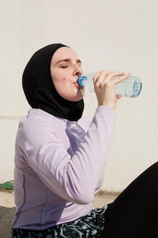Vrouw met purper jasje drinkwater