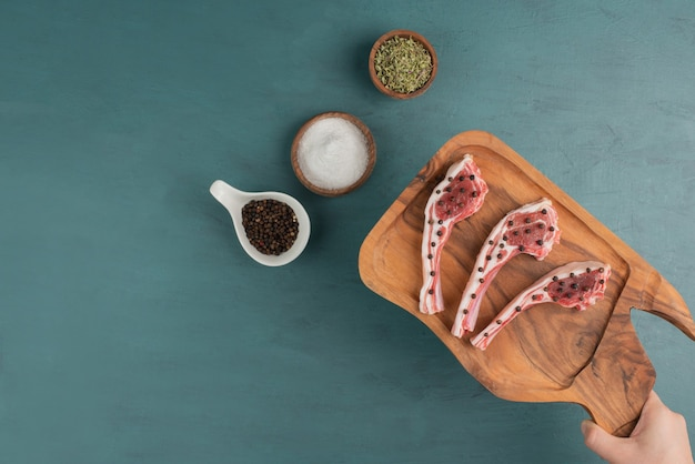 Vrouw met rauw vlees houten bord op blauwe tafel.