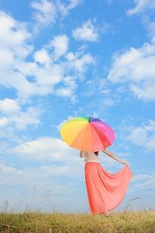 Vrouw met regenboogparaplu en blauwe hemel