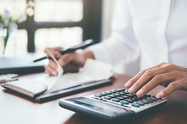 Vrouw met rekeningen en calculator. vrouw die calculator gebruiken om rekeningen te berekenen bij de lijst in bureau.