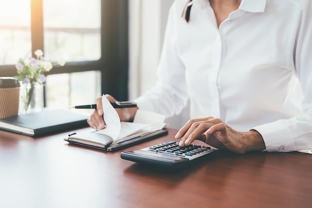 Vrouw met rekeningen en calculator. vrouw die calculator gebruikt om rekeningen bij de lijst in bureau te berekenen.