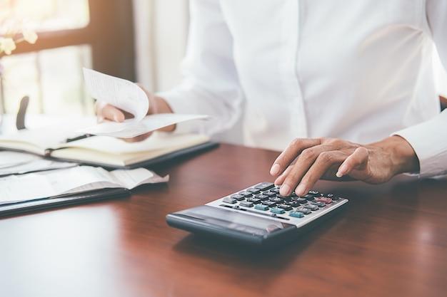 Vrouw met rekeningen en calculator.