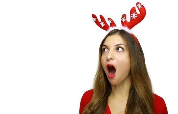 Vrouw met rendierhoorns op haar hoofd kijkt opzij