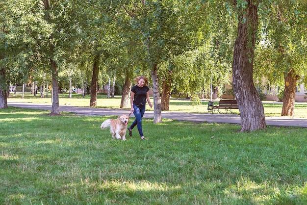 Vrouw met retrieverhond in het openluchtpark. uitzicht vanaf de afstand.