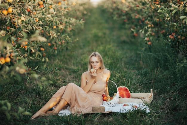 Vrouw met rijpe appel in een hand zittend op een witte deken