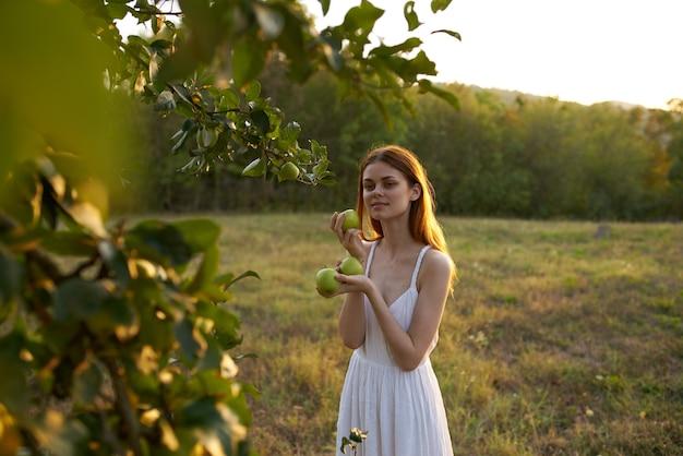 Vrouw met rijpe appels op een weiland met bergen en hoge bomen op de achtergrond.