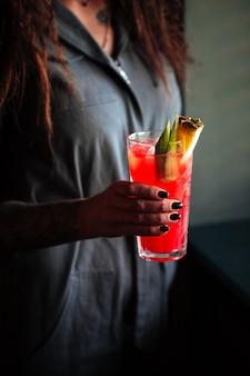 Vrouw met rode cocktail in een longdrinkglas met ijs en ananas