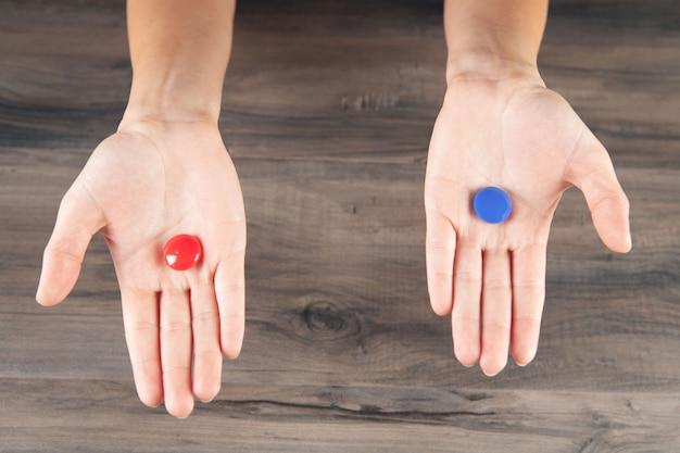 Vrouw met rode en blauwe pil in haar handen