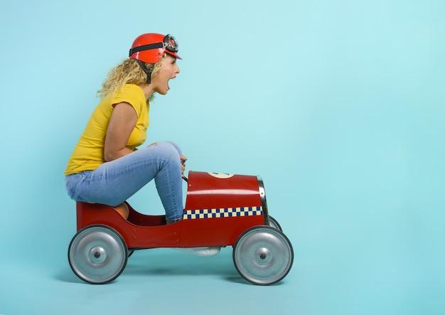 Vrouw met rode helm rijdt in een snelle speelgoedauto. cyaan achtergrond.