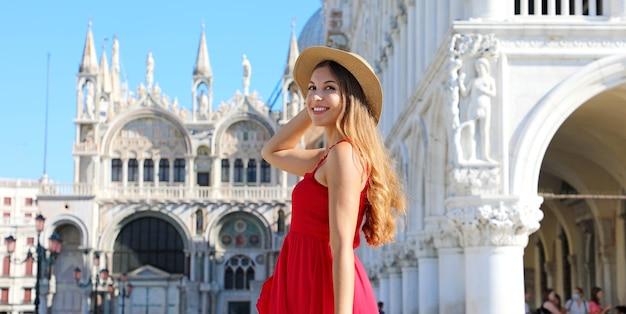 Vrouw met rode jurk poseren in het san marcoplein in venetië, italië. europa bestemming.