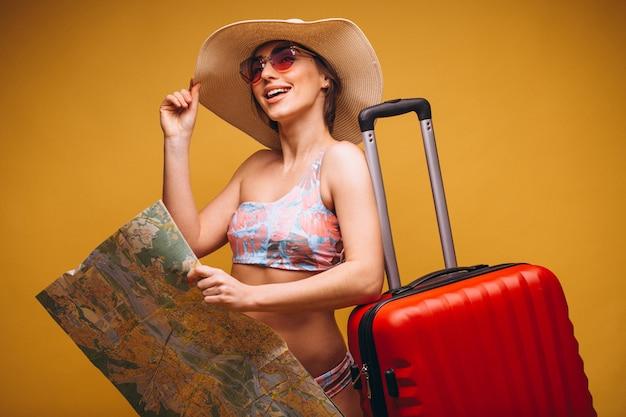 Vrouw met rode koffer en reizende kaart in een geïsoleerd zwemmen pak