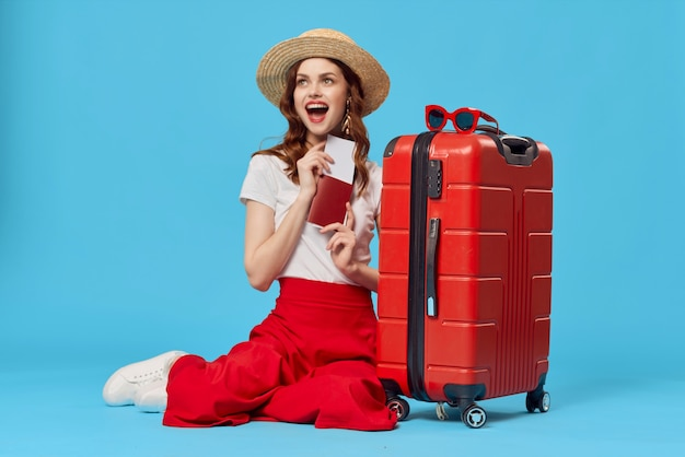 Vrouw met rode koffer zittend op de vloer van paspoort vliegtickets reizen blauwe achtergrond