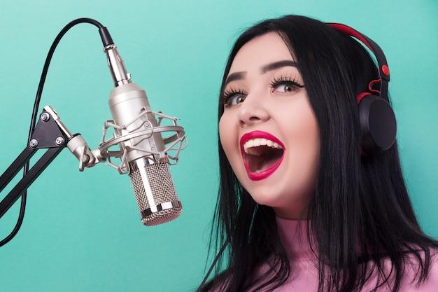 Vrouw met rode lippen zingen in de studio microfoon