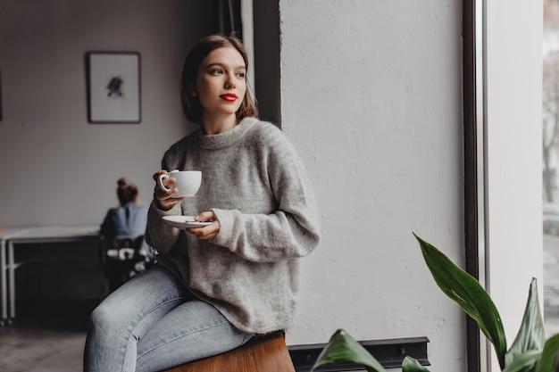 Vrouw met rode lippenstift gekleed in kasjmier trui zit op de vensterbank met kopje koffie op de achtergrond van het werkende meisje in kantoor.