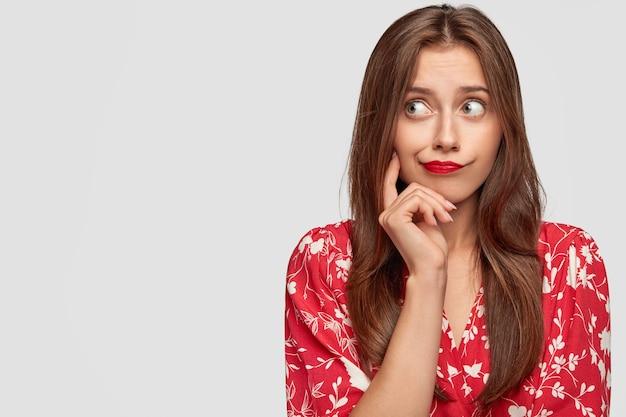 Vrouw met rode lippenstift poseren tegen de witte muur