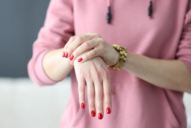 Vrouw met rode manicure die haar pols gezamenlijke close-up houdt. diagnose en behandeling van artritis