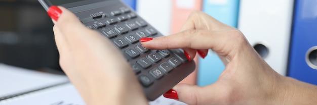 Vrouw met rode manicure die op calculator in bureauclose-up rekent