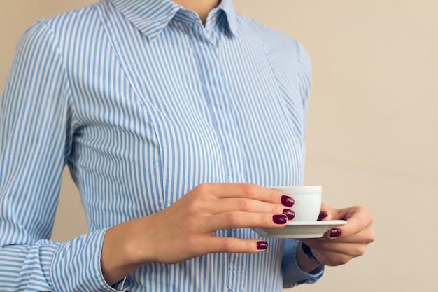Vrouw met rode manicure en blauw shirt met een kopje koffie close-up