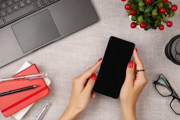 Vrouw met rode manicure met mobiele telefoon op grijze tafel