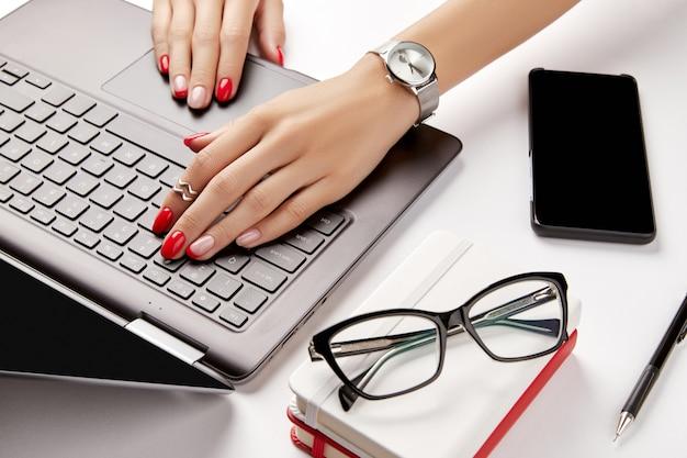 Vrouw met rode manicure werkt met laptop op witte tafel zakelijke dame werkt vanuit huis