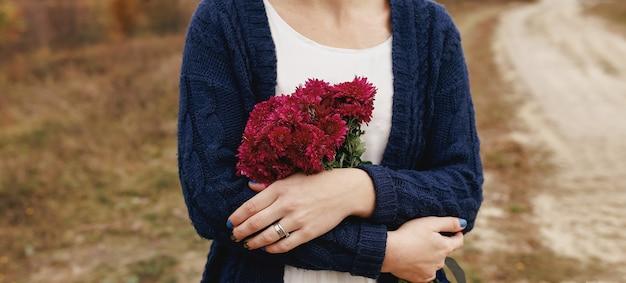 Vrouw met rode pioenrozen aanwezig van vriendje