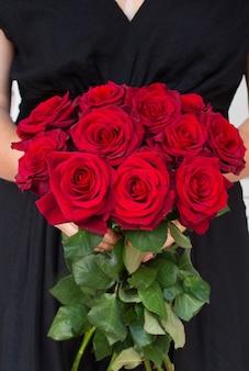 Vrouw met rode rozen ruiker close-up