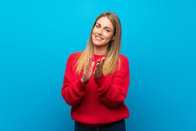 Vrouw met rode trui over blauwe muur applaudisseren na de presentatie in een conferentie
