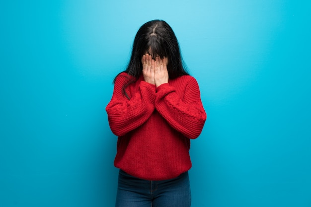 Vrouw met rode trui over blauwe muur met moe en zieke uitdrukking