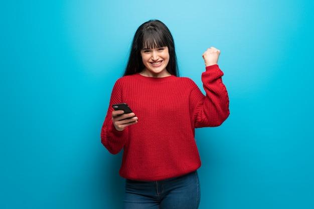 Vrouw met rode trui over blauwe muur met telefoon in overwinningspositie