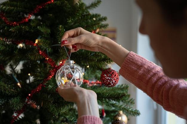 Vrouw met rode vakantiemanicure die transparante glanzende snuisterij thuis op een kerstboom hangt.