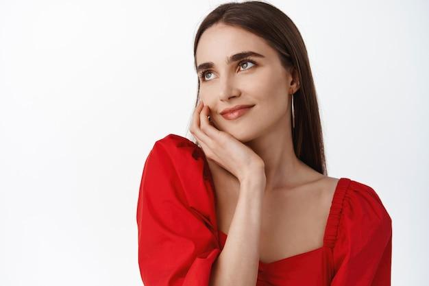 Vrouw met romantische blik, make-up op gezicht, wang aanraken en dromerig opzij staren, rode jurk op wit dragend